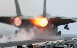 fighter jet takes off from an aircraft carrier