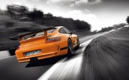 Orange Porsche GT3 RS in black and white road