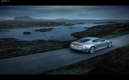 Silver Aston Martin car on the road, against the background of the lake with islands.