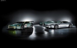 Three Aston Martin sports car on a black background with shadows.