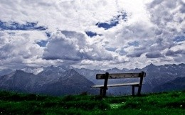 bench with a view of the mountains and the sky
