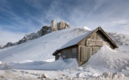 Wooden hut in the mountains after a snow avalanche