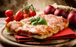 Appetizing pizza with basil leaves and tomatoes