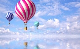 Flying balloons above the quiet surface of water