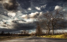 Beautiful sky with storm clouds, field and road