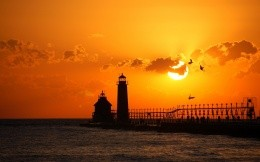 Sunset on the sea, pier, lighthouse and silhouettes of people