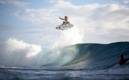 Jump on board surfing on the ocean wave.
