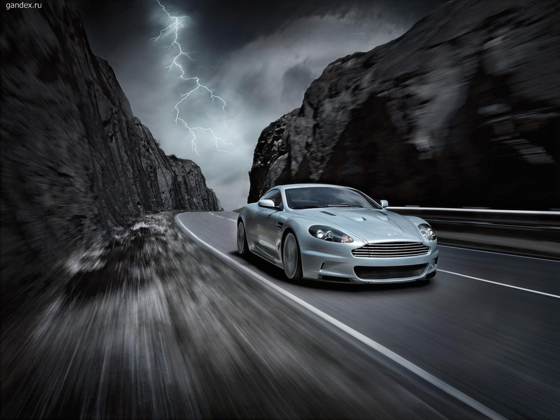 Aston Martin on the mountain road, traveling at high speed, the lightning in the sky.