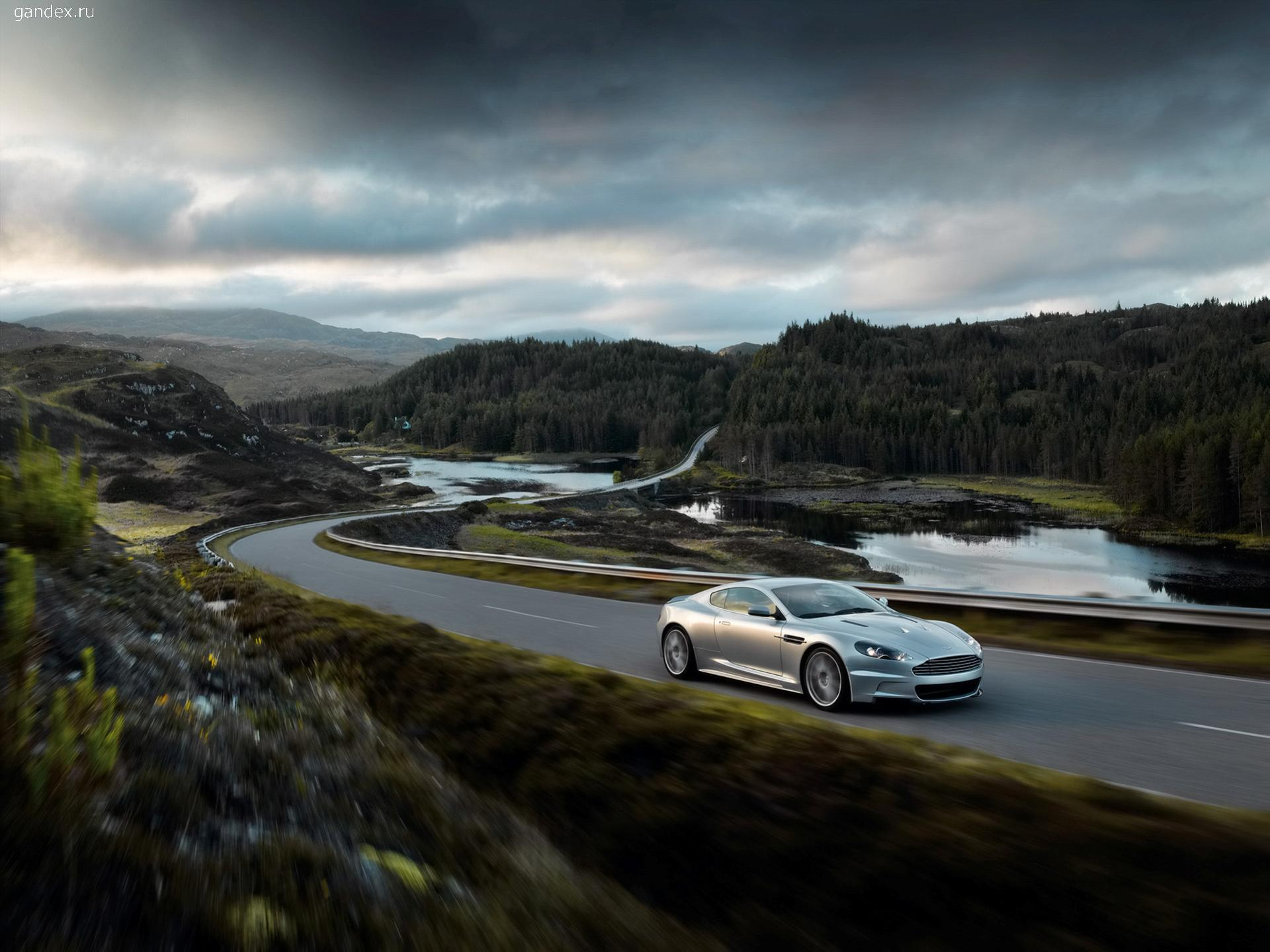 Aston Martin on the road against the background of the forest and the lake.