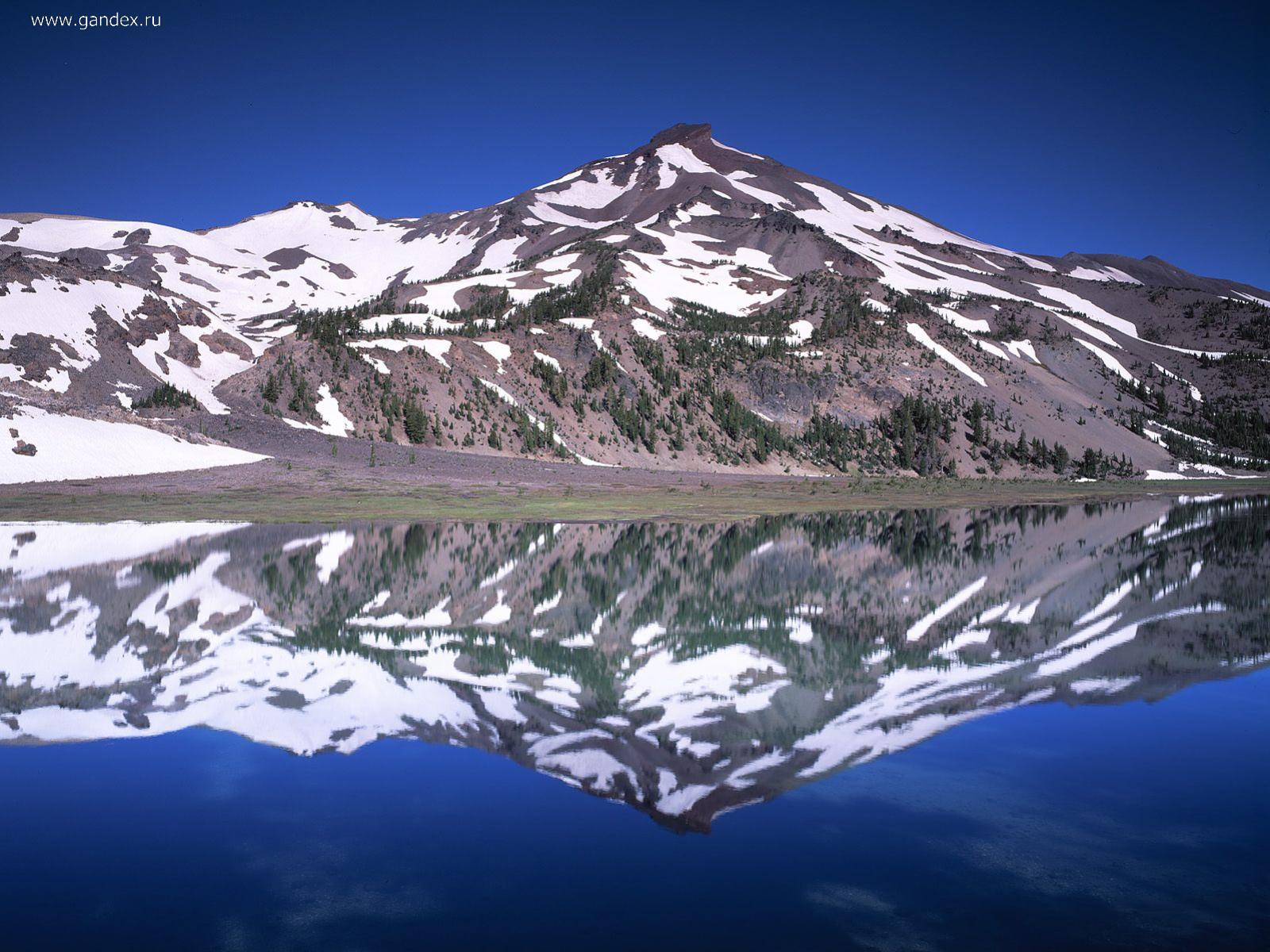 Snow-capped mountains and a cold mountain lake - wallpaper.