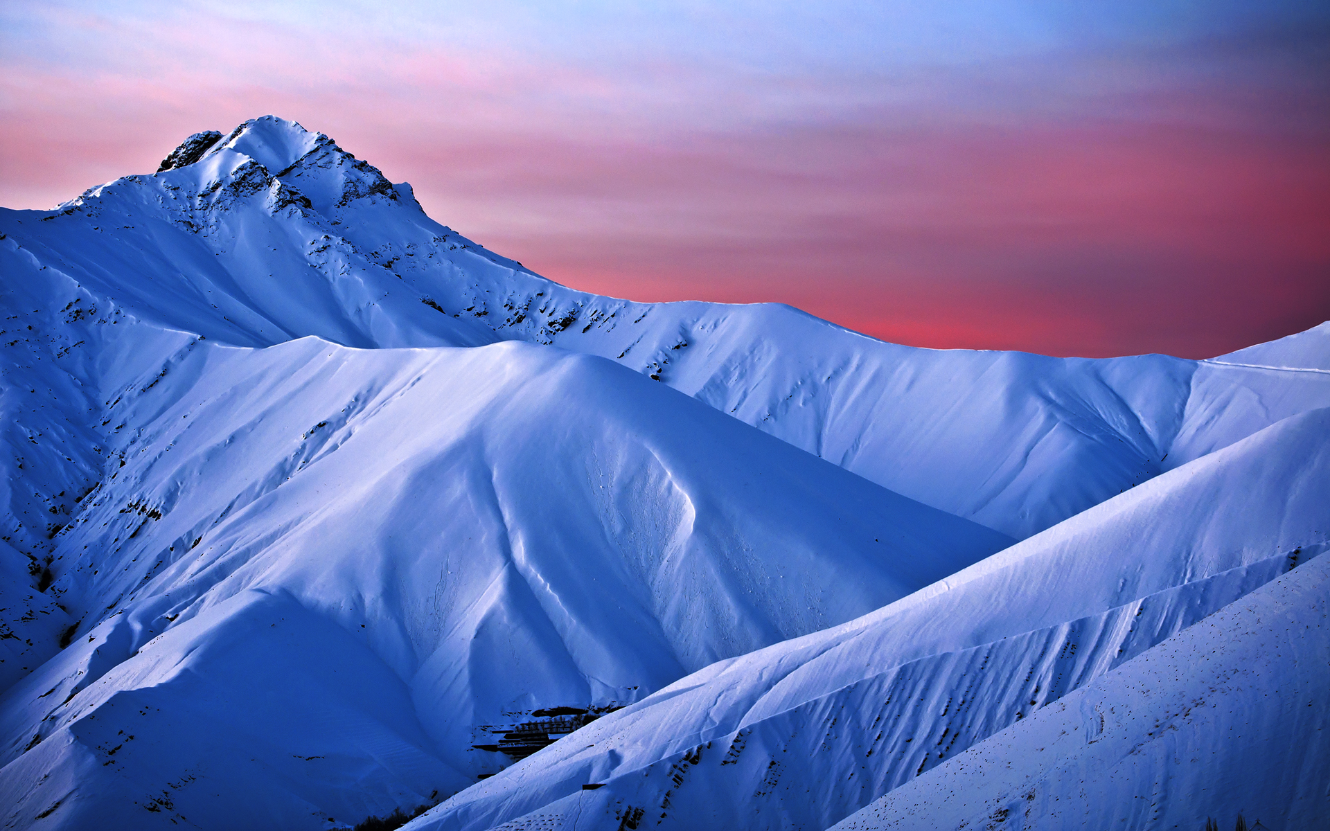 Snowy slopes and pink-blue sky.