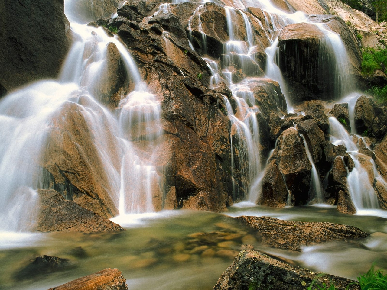 waterfall flows over a rock