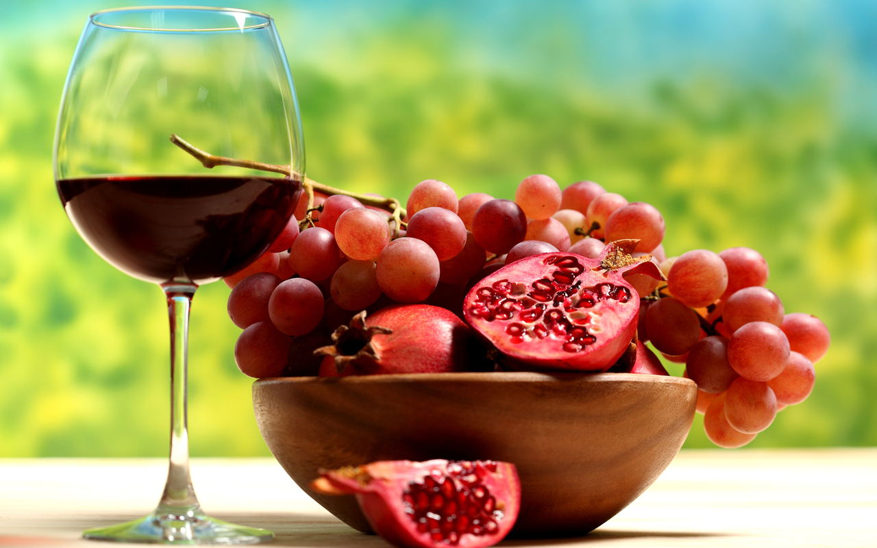 A glass of wine grapes and pomegranates