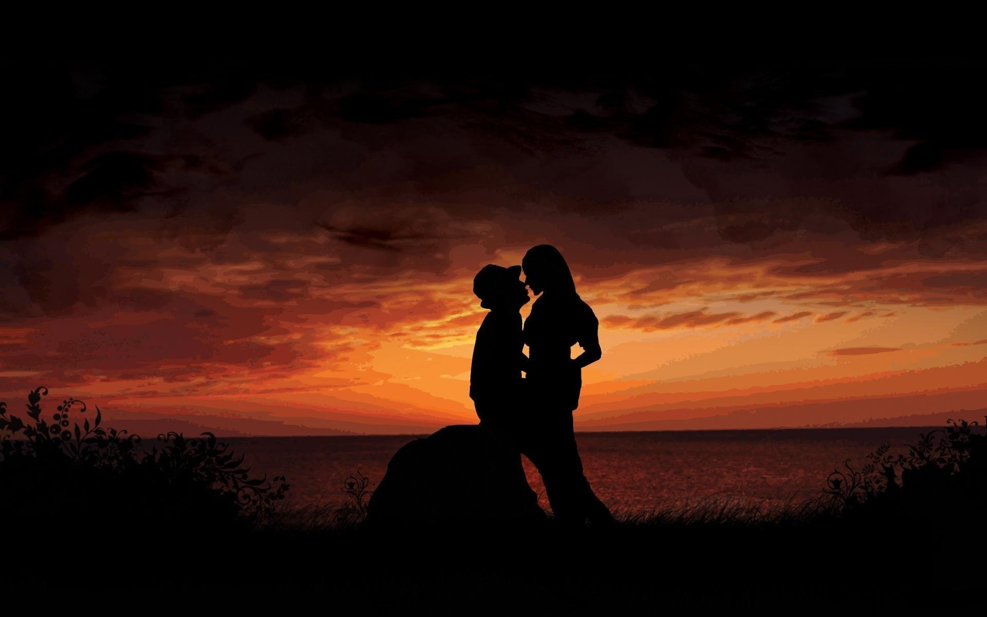 Love at sunset, a man and a woman, a passionate kiss.