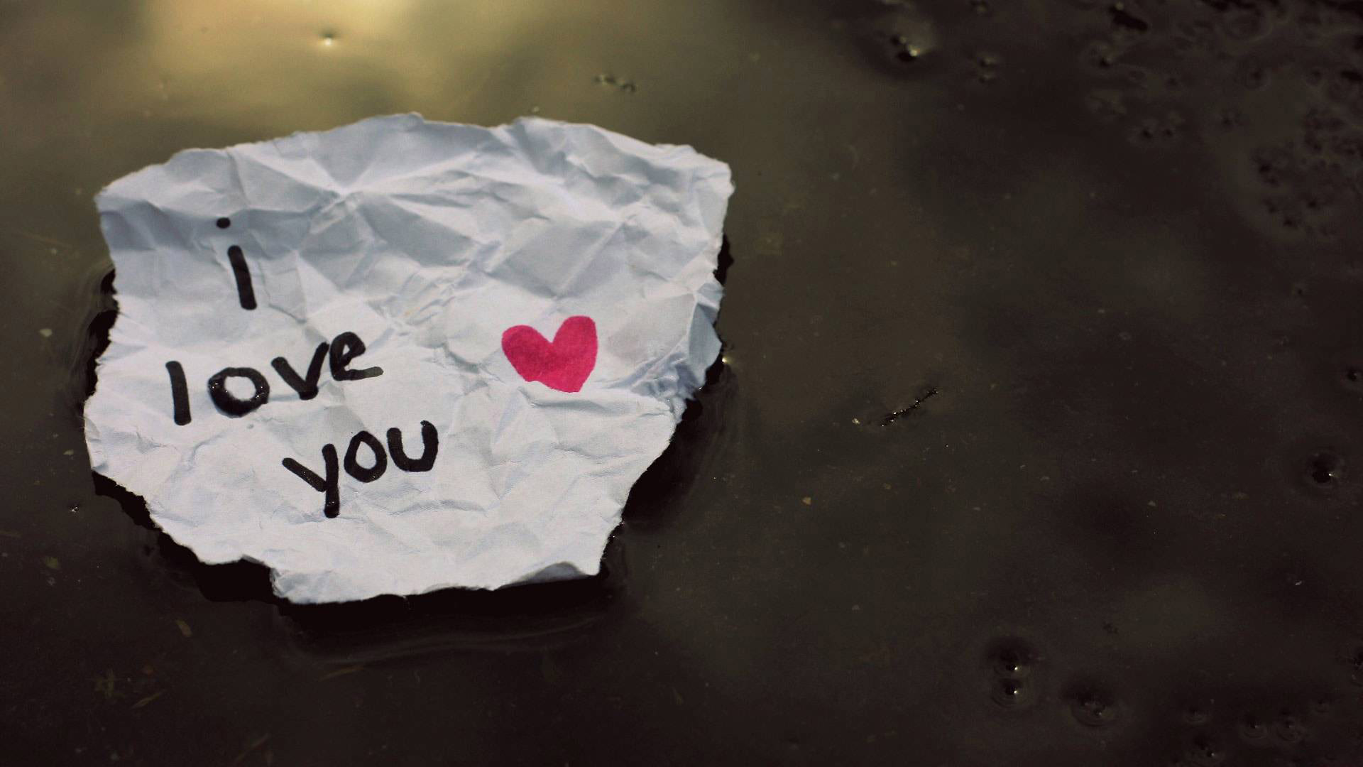 Love letter with the words I Love You in a pool of water